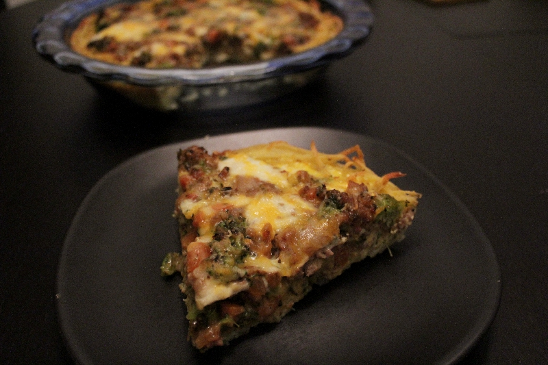 Slice of No-Recipe Quiche with Potato Crust with quiche in the background