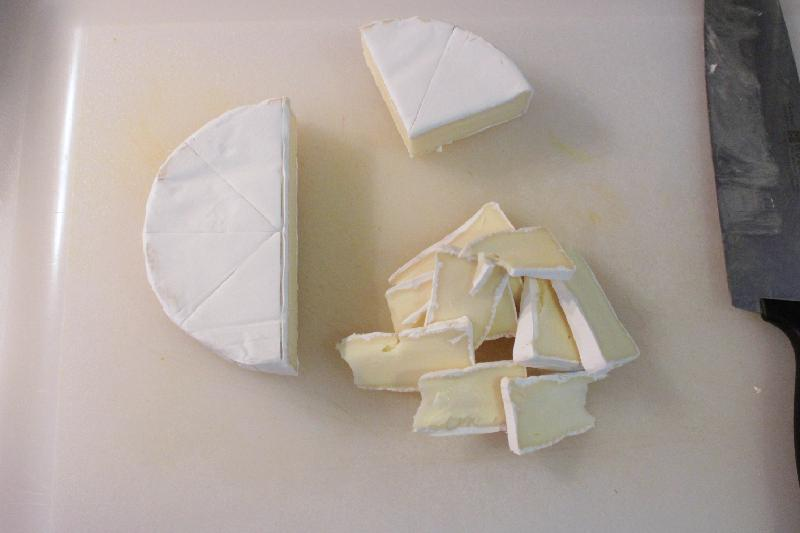Brie cheese wheel in slices on cutting board for bacon brie paninis