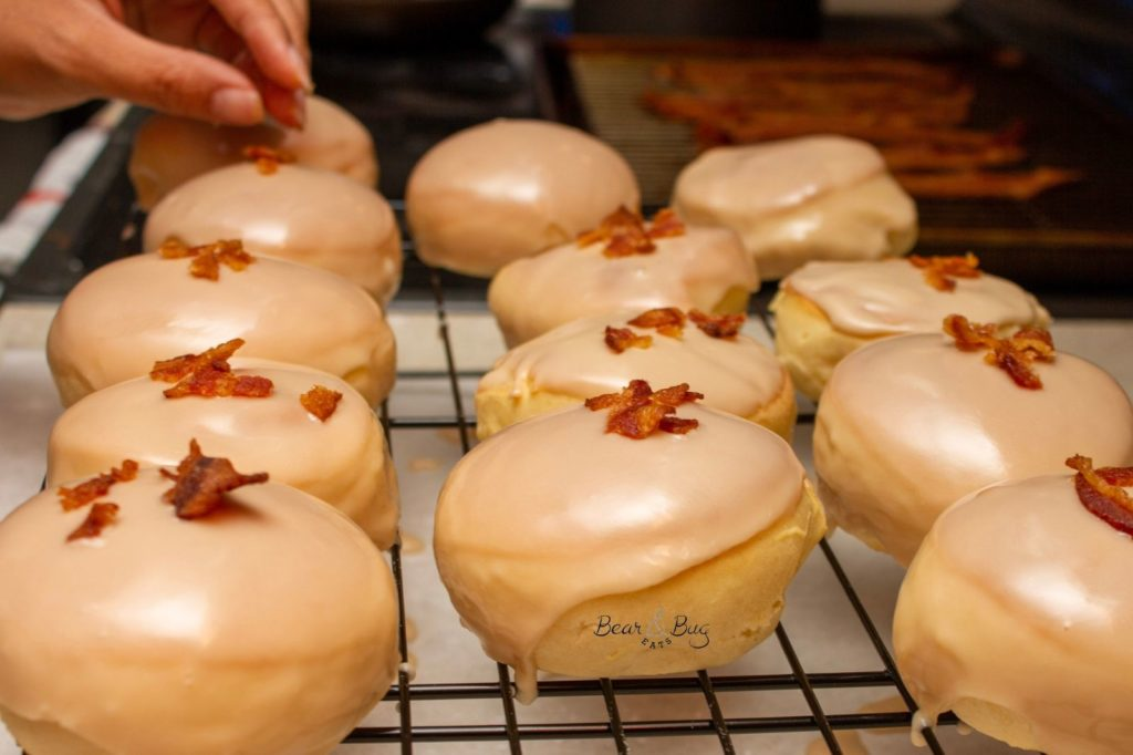 Hand placing bacon crumbles on top of glazed maple donuts