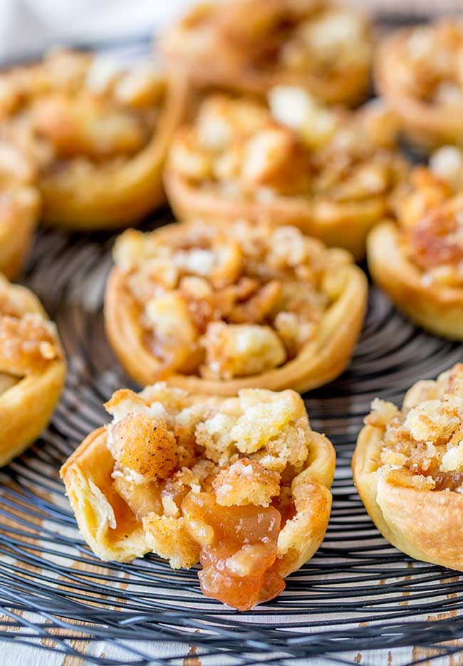 Closeup of a plate of tiny apple pies with donut crumb topping. the front pie has a little bit out.