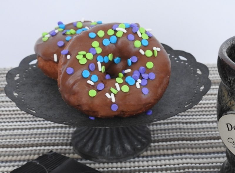 two chocolate-frosted donuts with colorful sprinkles on a cake stand