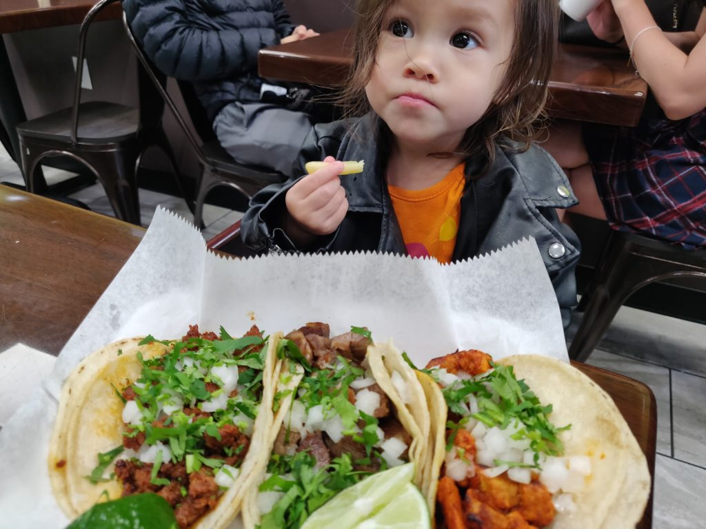 Toddler holding French fry in front of tacos