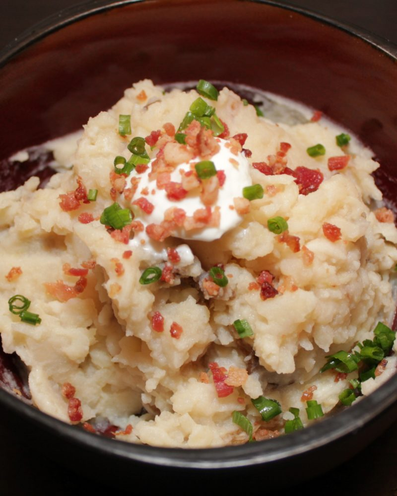 The best Slow Cooker Garlic Mashed Potatoes! Potatoes melt into broth and butter, then topped with bacon and chives | BearandBugEats.com