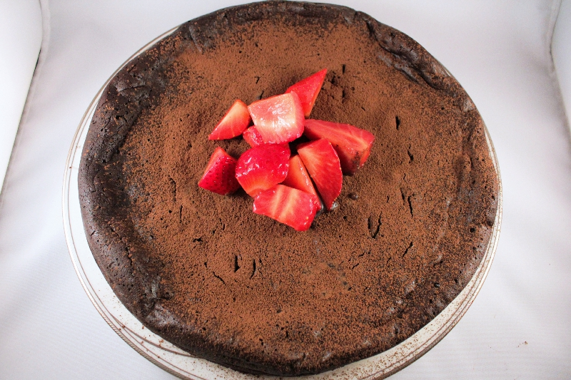 Flourless dark chocolate cake topped with macerated strawberries