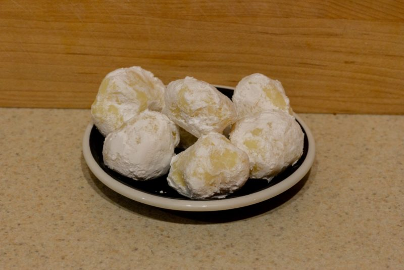 Several white chocolate lemon truffles on a small plate