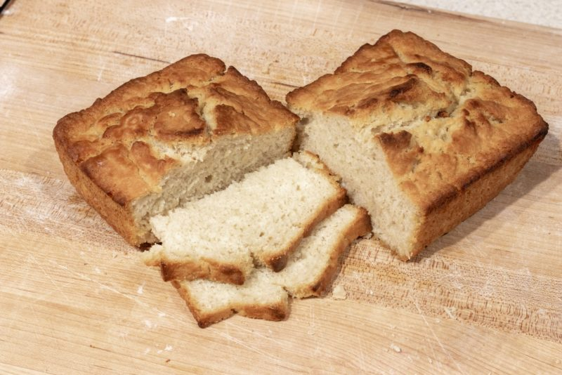 Two halves of beer bread loaf posed with two slices